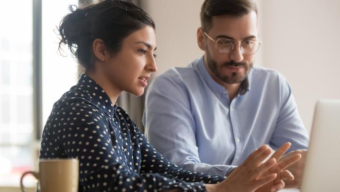 Man and woman at computer looking at Sage Fixed Assets